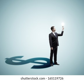businessman holding lamp and dollar shadow