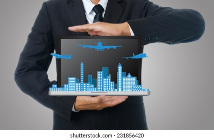 Businessman holding laptop with airplane travel around the city, for business and transport concept.