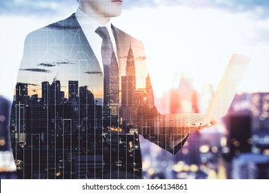 Businessman holding laptop with business statistics hologram on city background. Business and financial success concept.