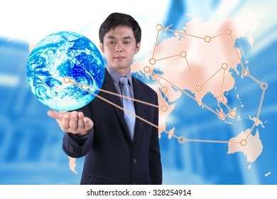 businessman holding laptop computer over blur office with imagine business line on global map