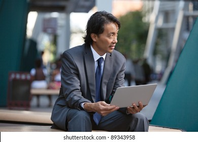 Businessman holding laptop and looking away