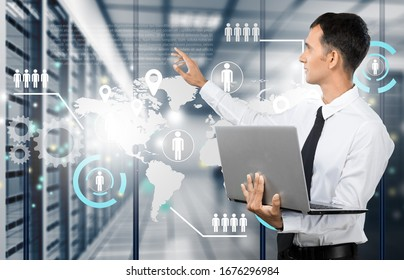Businessman holding laptop and touching icons on background