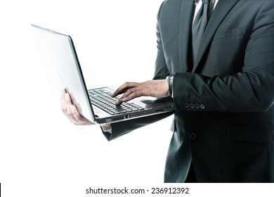 Businessman holding a laptop and typing isolated on white