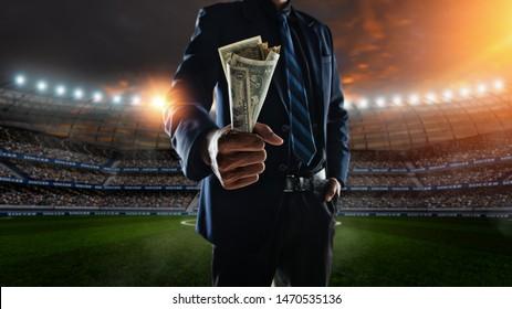 Geschäftsmann, der im Fußballstadion große Rechnungen im Hintergrund hält