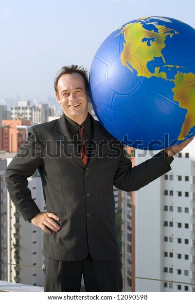 A businessman holding a large globe in one hand with his other hand on his hip.