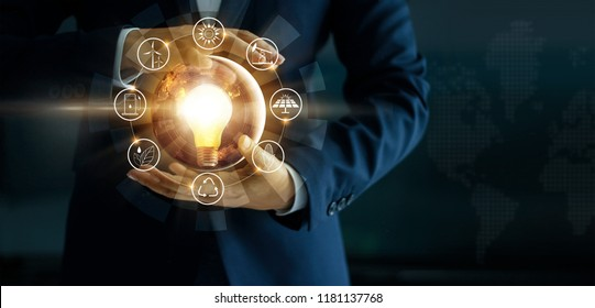 Businessman holding light bulb with energy sources icon. Campaigning for ecological friendly and sustainable environment. Earth day. Energy saving concept, Elements of this image furnished by NASA
