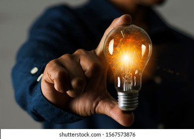 A businessman holding a light bulb in his hand demonstrates the broad vision and concept of building a business that will grow with efficiency and stability.