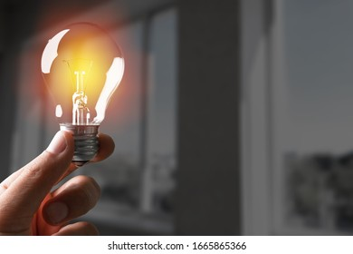 A businessman holding a light bulb in his hand