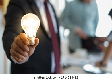 Businessman holding the light idea bulb show new good smart idea thinking and creative innovation business with group of people thinking, brainstorming and planning background.