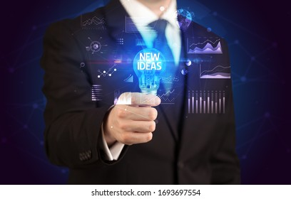 Businessman holding lightbulb with NEW IDEAS inscription, Business idea concept