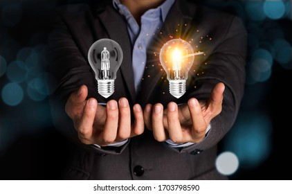 Businessman holding lightbulbs which one lamp glowing and one lamp black out.Creativity idea concept.