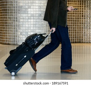 Businessman holding luggage and using mobile phone