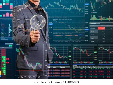 businessman holding magnify glass verifying stock trading screen