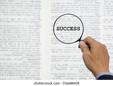 Businessman holding magnifying glass and word SUCCESS with blurred background of book page, business  concept.