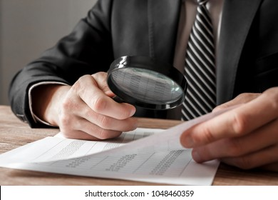 Businessman holding magnifying glass zoom and analyzing financial indicators