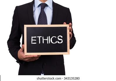 Businessman holding mini blackboard with ETHICS message