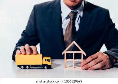 Businessman holding a miniature of house and delivery toy truck, indicating the concept of direct delivery to house, moving relocation and freight service.