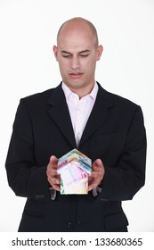 A businessman holding a miniature house made out of bills.