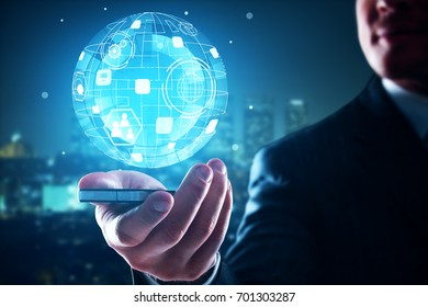 Businessman holding mobile phone with business globe projection on blurry night city background. Global business concept. 3D Rendering