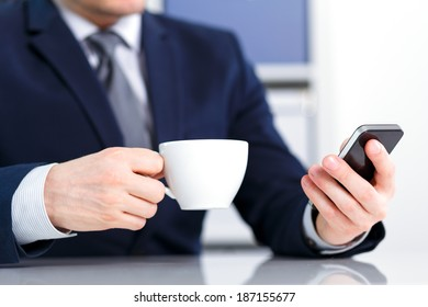 Businessman holding a mobile phone and a cup of coffee