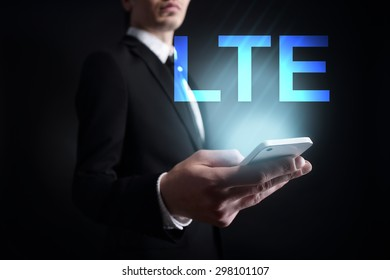 """Businessman holding a mobile phone with """"LTE"""" text on virtual screen. Internet concept. Business concept."""