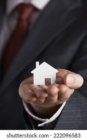 Businessman Holding Model House In Palm Of Hand