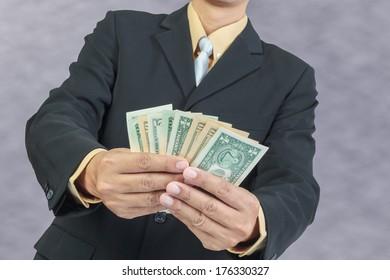 Businessman holding Money Cash Dollars in hands, finance concept