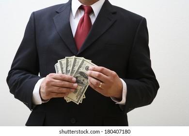 Businessman holding money isolated on white
