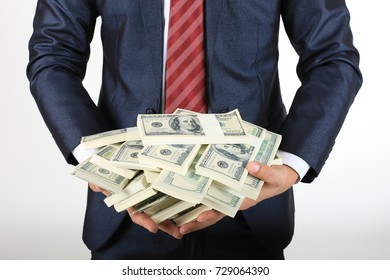 Businessman holding a lot of money on white background.