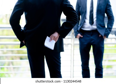 Businessman holding money in white envelope behind his back conceptual of, bribe, graft or corruption, cropped closeup the bribe the concept of corruption and anti bribery