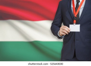 Businessman holding name card badge on a lanyard with a flag on background - Hungary