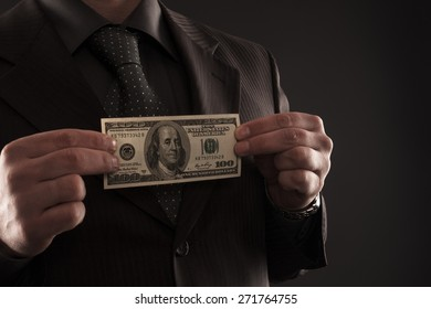 Businessman holding one hundred dollars bill in his hands in front of chest.