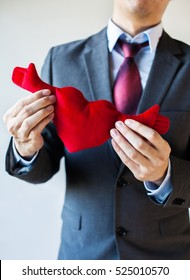 Businessman holding open armed heart with hands - warm welcome and invitation with heart concept.