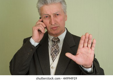 businessman holding out his hand and talking on the phone