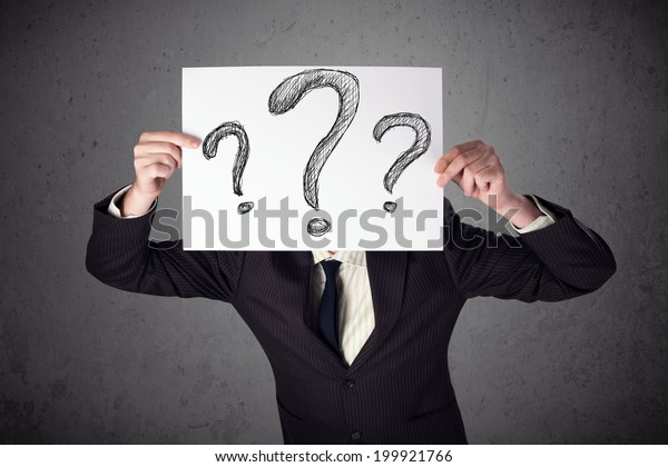 Businessman holding a paper with drawed question marks on it in front of his head