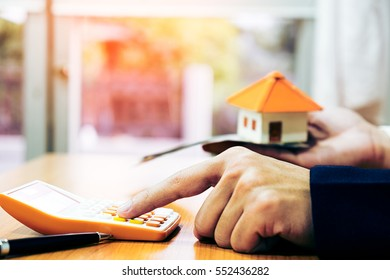 Businessman holding paper home model. Loan concept
