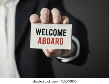 Businessman holding paper with text Welcome Aboard. Businessman holding card. Business concept.