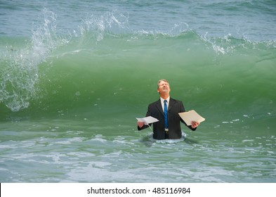 Businessman holding paperwork getting ready to be hit by a big wave representing drowning in business pressure, deadlines, work stress, overworked, problems and problem solving.
