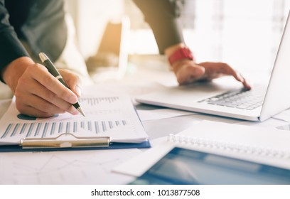 Businessman holding pen and pointing paper chart summary analyzing annual business report with using laptop at room office desk.