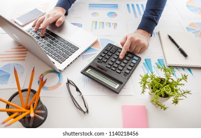 Businessman holding a pen is working with graph documents and sunset light background. Stock market chart and finger pointing on tablet in office.