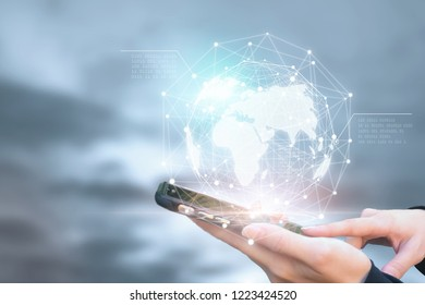 Businessman holding phone in hand with global connection concept.