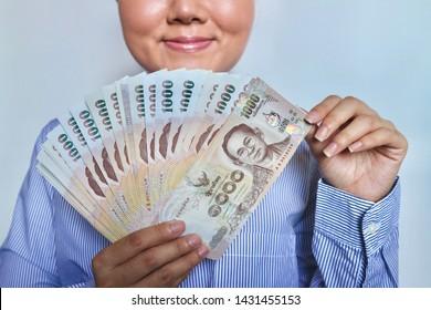 Businessman holding pile of Thai Baht money