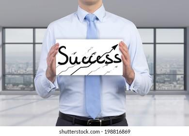 Businessman holding a poster 'success'
