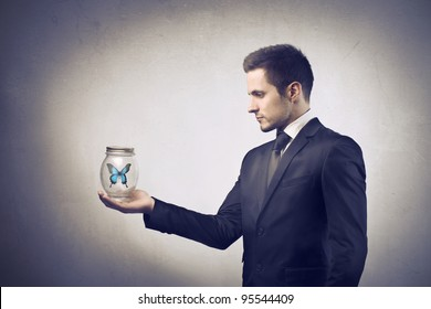 Businessman holding a pot with butterfly in it