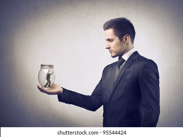 Businessman holding a pot with tiny businessman in it