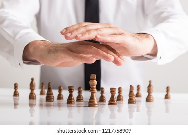 Businessman holding protective hands above chess pieces placed on office desk with king in the leading position.