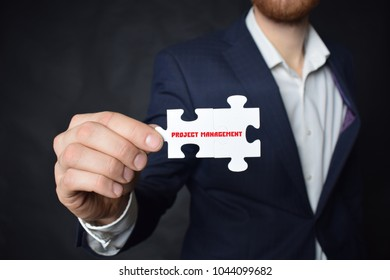 Businessman holding a puzzle with the inscription:PROJECT MANAGEMENT
