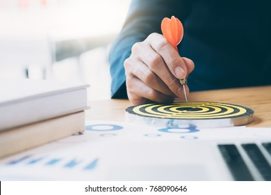 Businessman holding red dart push on target. Business strategy planning success target goals. Business development concept