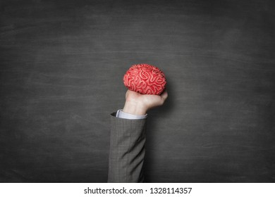 Businessman holding red toy brains