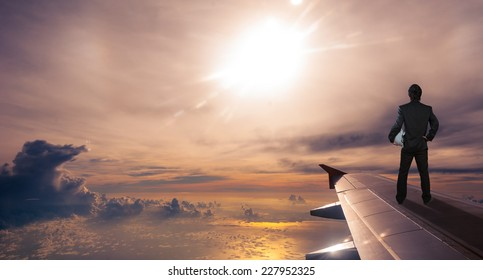businessman holding safety helmet standing on airplane wing, successful business concept